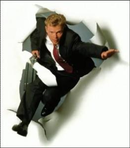 man jumping through paper
